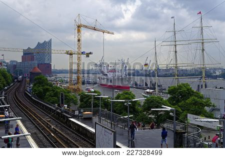Historic Harbor In Hamburg With Ships And Docks In The Background And Harbor Facility With Belfry In