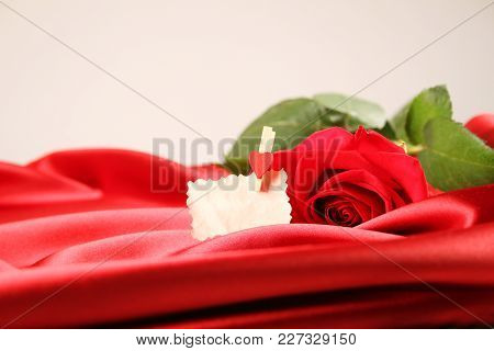 Close-up Of A Large Red Rose On Satin. Background