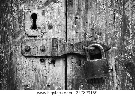 Old Lock And Rusted Keyhole On Wooden Door, Black And White Photo