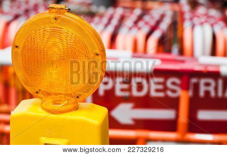 Yellow Warning Light And Red Street Barriers On A Border Of Construction Site
