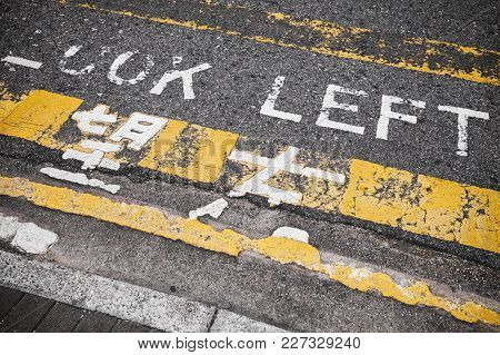 Look Left. Caution Road Marking For Pedestrians Shows Direction Of Approaching Traffic In Hong Kong