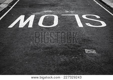 Slow, White Text Road Marking Over Black Urban Asphalt Pavement, Background Photo