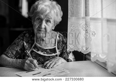 Retired woman fills out utility bills sitting at the table.