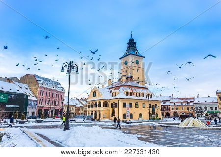 Brasov, Romania - February 18, 2018: Main Square Of The City With Pigeons Flying Near The Council Ho