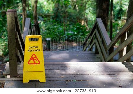 Yellow Caution Slippery Wet Floor Sign Outdoors Near Wooden Staircase On Forest