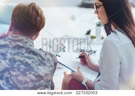Serious Mental Problems Help. Selective Focus On A Young Psychotherapist Holding A Clipboard And Tak
