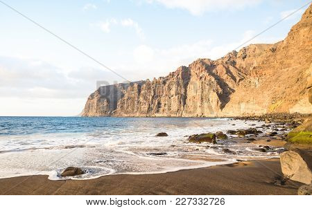 Desert Solitary Beach In Tenerife With Los Gigantes Cliffs On Background - Travel Concept With Natur