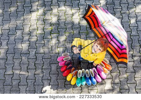 Little Kid Boy And Group Of Colorful Rain Boots. Blond Child Standing Under Umbrella. Close-up Of Sc