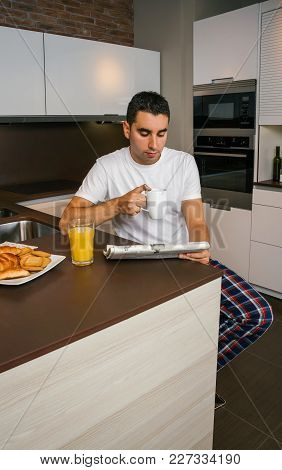 Young Man Having Breakfast In The Kitchen And Reading The Newspaper