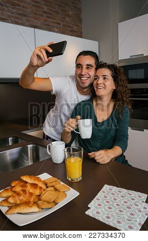 Couple Having Breakfast In The Kitchen While Taking Selfie