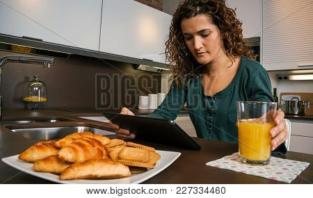 Young Woman Having Breakfast In The Kitchen And Looking At The Tablet