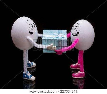 Funny Miniature Easter Egg Boy Gives A Gift Present Box To Happy Egg Girl.