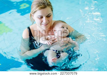 Happy Middle-aged Mother Swimming With Cute Adorable Baby In Swimming Pool. Smiling Mom And Little C