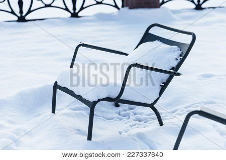 Meatl Chair Covered With Snow In Small Park. Natural Background. Winter Season. Copy Space. Metal Fu