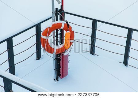 Lifebuoy Against Snow Background. Life Preserver Next To Frozen Winter Pond Or River Covered With Ho