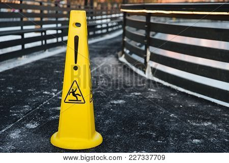 Close Up Shot Of Yellow Warning Sign Stands On Gray Asphalt Covered With Snow, Warns About Wet Road