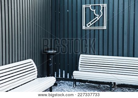Smoking Area With Ash Bin And Two White Benches For Relaxation. Sign On Cigarette On Fence. Special