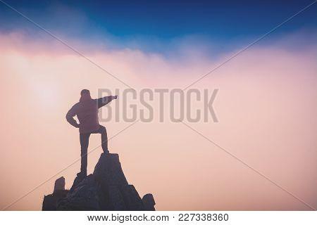 Hiker Standing On A Rocky Cliff And Points To The Sky. The Top Of The Mountain. Instagram Stylisatio