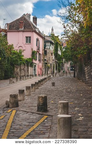 Cobblestone Road Moving Up The Hill Of Montmartre Passing Pink House And Other Old Buildings In Autu