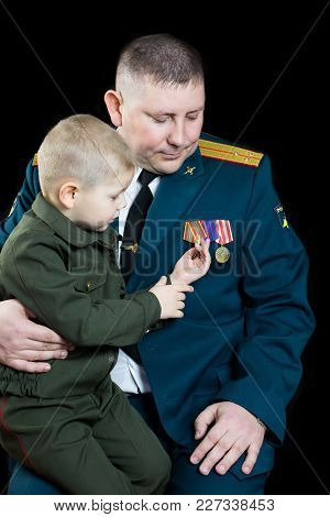 A Small Boy In Military Uniform Looks At Military Medals.