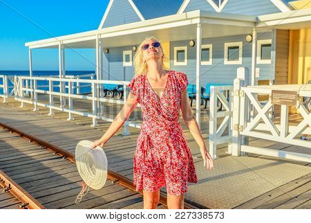 Carefree Blonde Woman Enjoys The Sunset Light On Famous Busselton Wooden Jetty In Busselton, Western