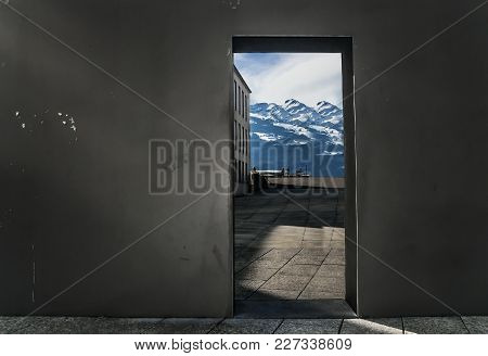 A Beautiful Pure Scene Of High Snowy Mountains And A Clear Blue Sky Visible Through A Doorway Of A G