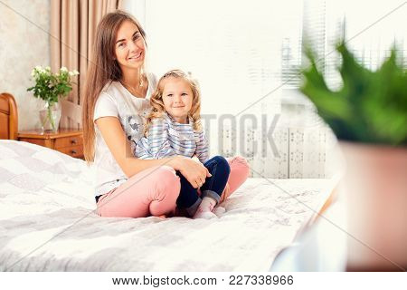 Portrait Of Mother And Daughter On The Bed By The Window. Mothers Day.
