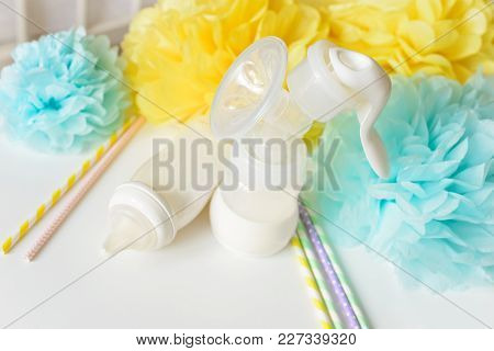 Breast Pump And Baby Bottles With Milk, Various Festive Paper Decor In Front Of Baby Bedroom. It's A