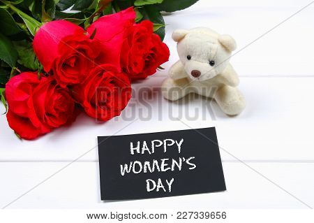 Happy Woman's Day. March 8. Roses, Teddy Bear And Chalkboard On A White Wooden Table.