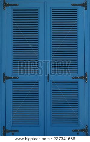 Large Window Closed By Blue Shutters. Vertical Photo.
