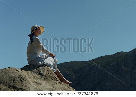 Young Girl In Hat Sits On A High Stone Hill Enjoy The Beautiful Nature Against The Background Of The