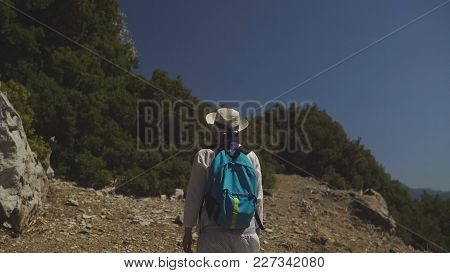 Young Tourist Girl In Hat And With Backpack Smiling And Walking Along The Trail Among Beautiful Natu
