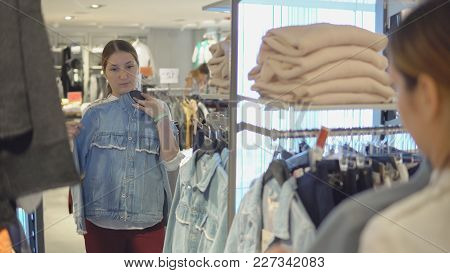 Lovely Girl Looks At Her Reflection In The Mirror While Trying On Clothes In Fashion Store While Sho