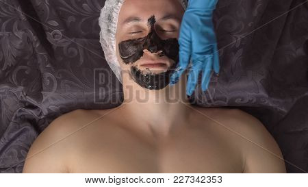 Applying A Black Cosmetic Mask To The Face Of A Handsome Man In A Spa Salon