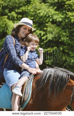 Young Woman With A Young Son Rides A Horse In The Summer In The Park