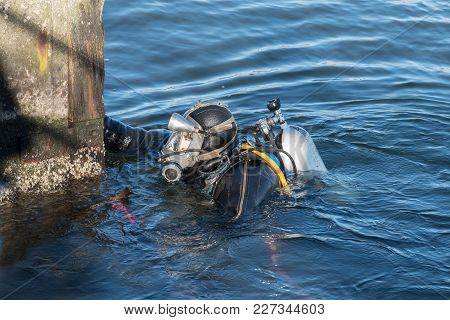 Industrial Diver With Scuba Gear, Diving Helmet And Protective Suit Working In The Water At The Shor