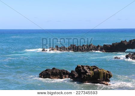 Volcanic Rocks Along The Coast Line With Waves Lapping On The Shore.