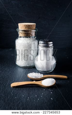 Different Types Of Salt With Spoons And Jars On Dark Background. Sea Salt And Kitchen Salt