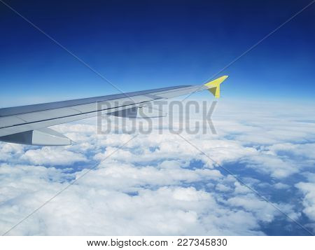 Airplane With Yellow End Above White Clouds In The Blue Horizon Somewhere Above Europe
