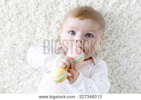 Cute Adorable Newborn Baby Playing With Colorful Pastel Vintage Rattle Toy. New Born Child, Little G