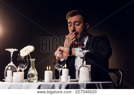 Handsome Man Looking At Watch And Yawning While Waiting For Romantic Date In Restaurant