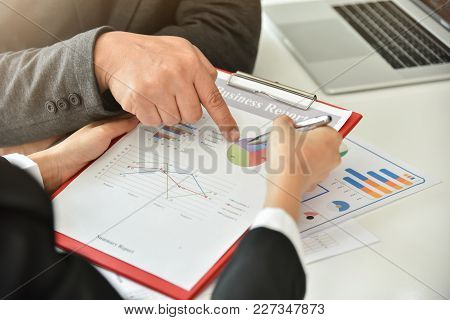Businessman And Businesswoman Are Discussing At Meeting. Business People Hands Are Pointing On Chart