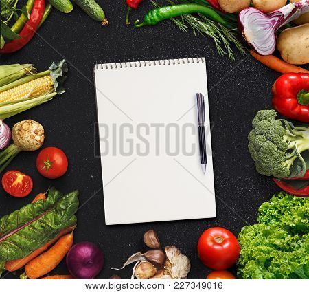 Notepad For Ingredients List And Frame With Fresh Vegetables On Black Background. Mockup For Healthy