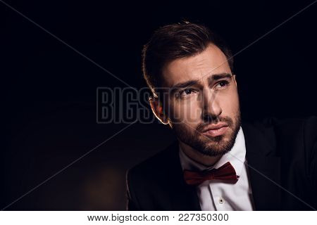 Sad Bearded Handsome Man In Jacket And Bow Tie, Isolated On Black