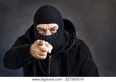 A Man In A Balaclava On A Dark Background. Copy Space. Concept Stealing, Deception, Kidnapping