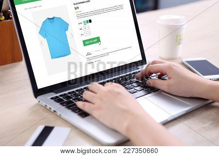 People Buying Running Shirt On E-commerce Website With Smart Phone, Credit Card And Coffee On Wooden
