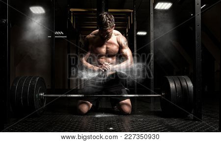 Muscular man clapping hands and preparing for workout at a gym. Focus on dust