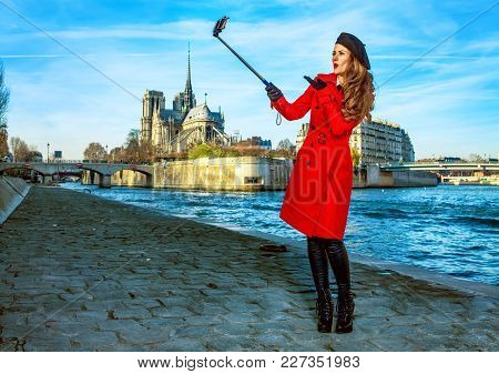 Bright In Paris. Happy Young Traveller Woman In Red Trench Coat On Embankment Near Notre Dame De Par