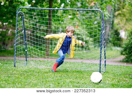 Active Cute Little Kid Boy Playing Soccer And Football And Having Fun, Outdoors. Child Having Game O