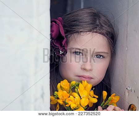 Young Girl Wearing Floral Headband, Holding Yellow Flowers, Staring At Camera, Between Wall And Open